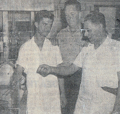 Three men in a black and white photograph speaking in a pizza kitchen.